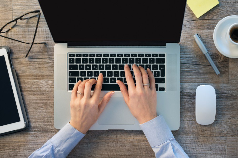 Businesswoman hands typing on laptop