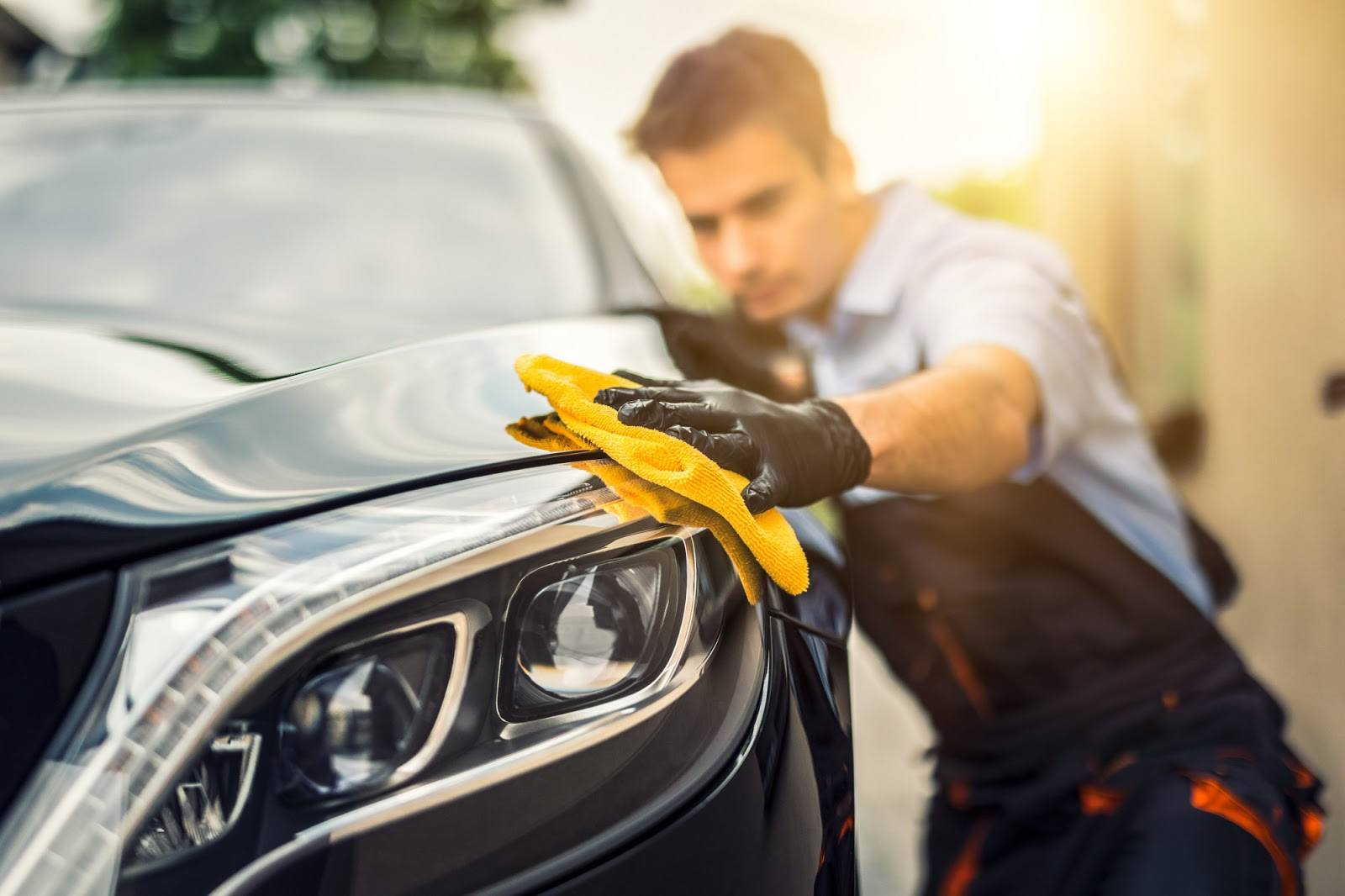 A detailer waxes the side of a car using a microfiber.