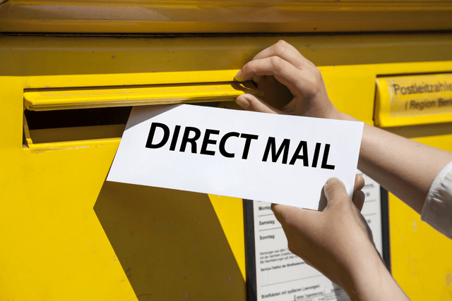 An image of someone putting a direct mail piece in a mailbox.